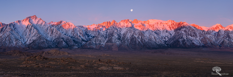 The rising sun to the east casts the peaks of the Eastern Sierra mountains in a fiery orange glow below a setting waning gibbous moon.