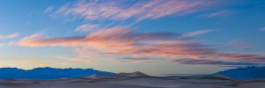 Sunset light paints clouds pink above sand dunes and mountains in Death Valley National Park