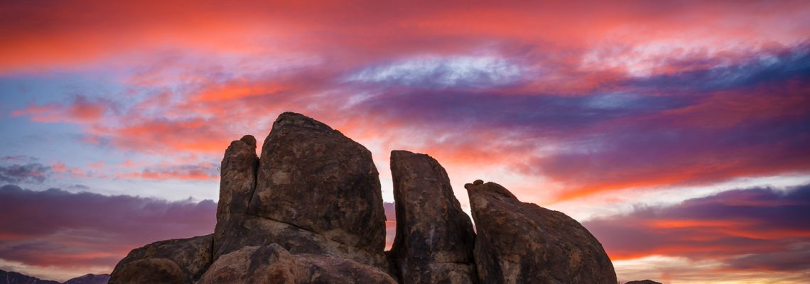 A vibrant sunrise paints the clouds above a group of boulders in the Alabama Hills in California.