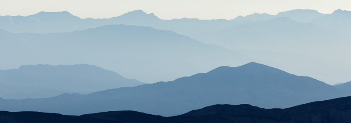 Varying shades of blue formed by distant mountains, the rising sun, haze and dust near Death Valley National Park.