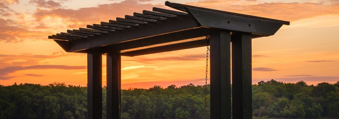 A riverside bench swing under a magnificent sunrise sky