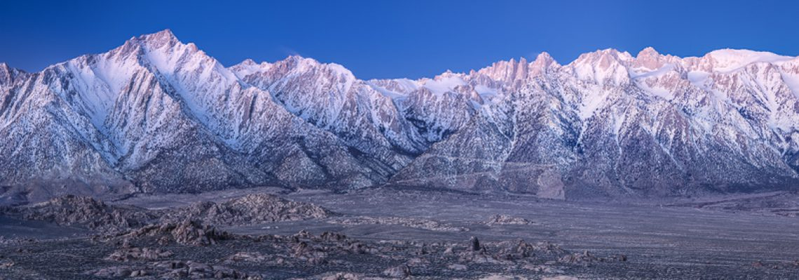 The blue light of dawn illuminates the snow-covered Eastern Sierra under a setting moon.
